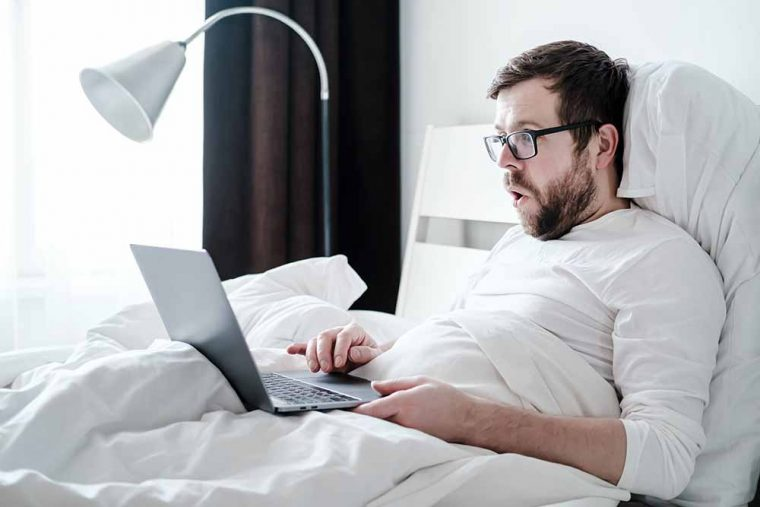 Morning of a successful freelancer. Surprised, satisfied man in pajamas works with a laptop, lying in a soft bed, in natural light